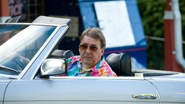 Un homme en chemise bariolée et avec des lunettes de soleil au volant d'une décapotable.