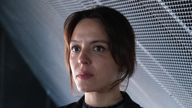 Une femme aux cheveux bruns. Elle affiche un air sérieux.