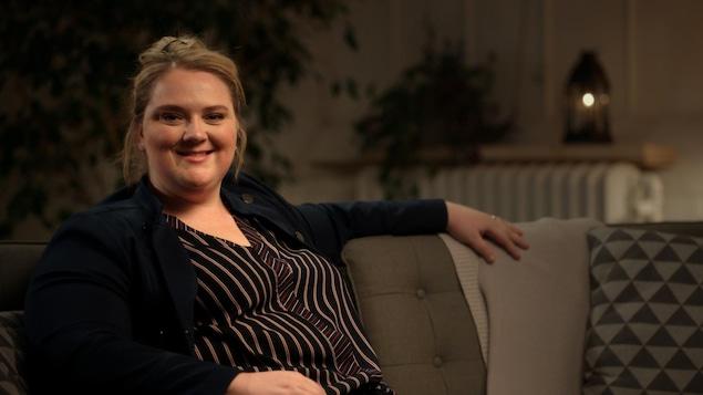 Elle est assise dans un canapé, souriante.