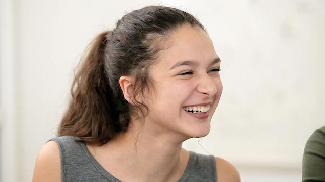 Une jeune femme qui rit. Ses cheveux sont attachés en queue de cheval.