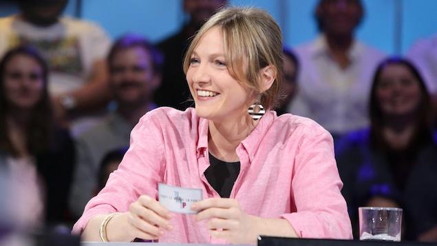 Elle porte un t-shirt noir et une chemise rose. Elle tient dans ses mains une carte de Dany. Elle sourit.