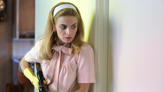 Elle se tient contre un mur avec une arme.