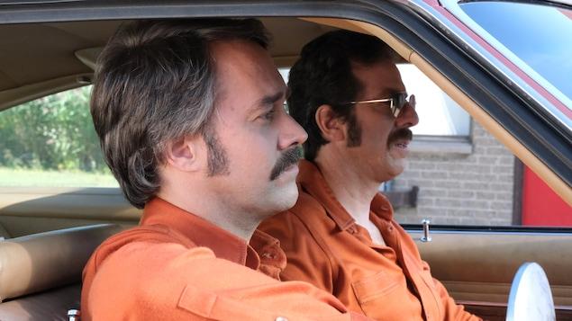 Les deux hommes sont dans une voiture.