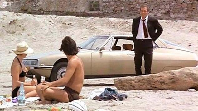 Un couple assis sur la plage en maillots de bain regarde un autre homme en costume, devant sa voiture