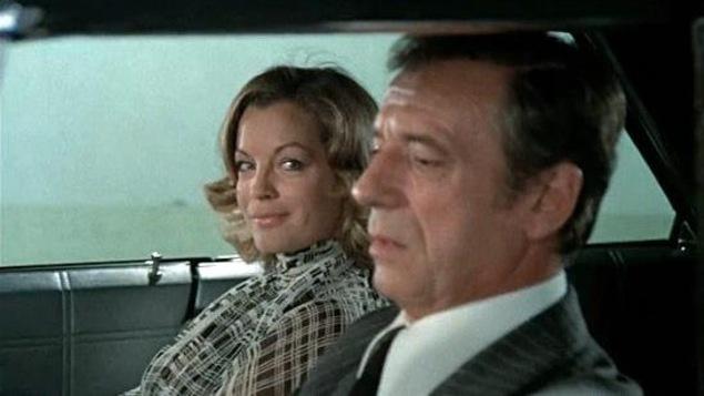 Assise à côté de lui, une femme regarde un homme qui conduit une voiture