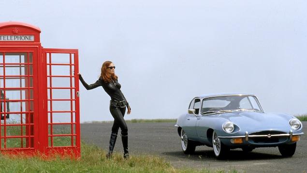 Une femme en tenue de cuir moulante prend appui sur la porte d'une cabine téléphonique rouge, à côté d'une voiture de sport.