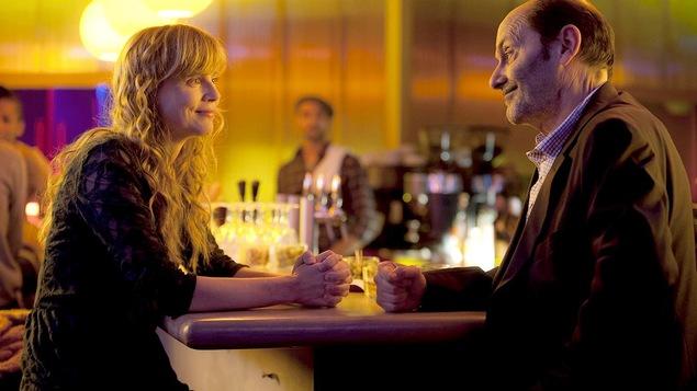 Un homme (Jean-Pierre Bacri) et une femme (Isabelle Carré) face à face, souriants, dans un bar.