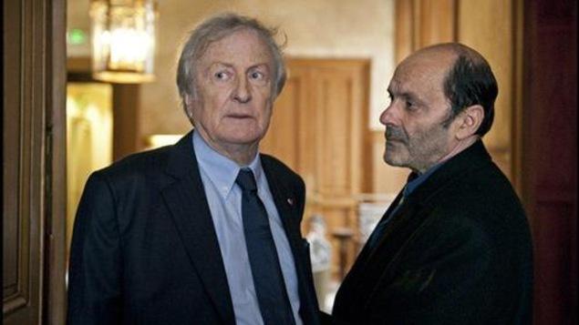 Deux hommes (Claude Rich et Jean-Pierre Bacri) dans un encadrement de porte.