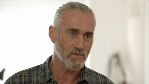 Ses cheveux, gris, sont attachés. Il a les yeux bleus. Il porte une chemise à carreaux.