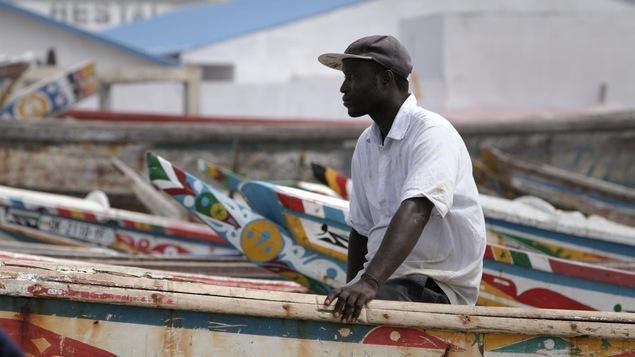 Un homme est assis sur des bateaux amarrés.