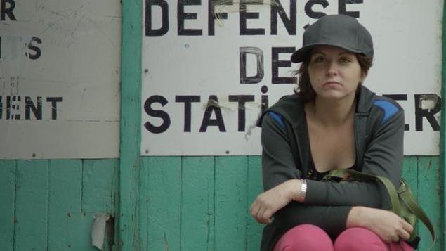 Une femme se tient accroupie sur un mur où il est écrit défense de stationner.