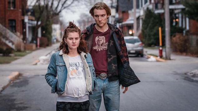 Une jeune femme enceinte et un jeune homme qui la regarde durement.