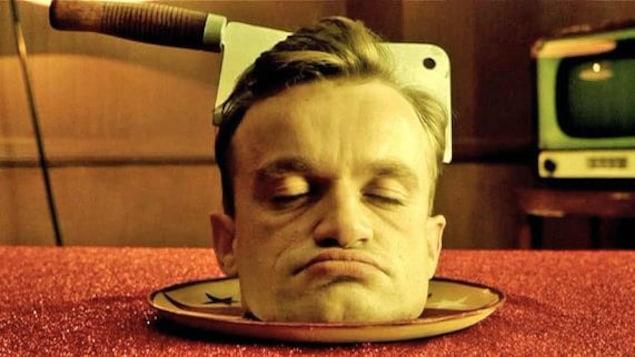 Une tête d'homme dans une assiette avec une machette en travers du crâne.