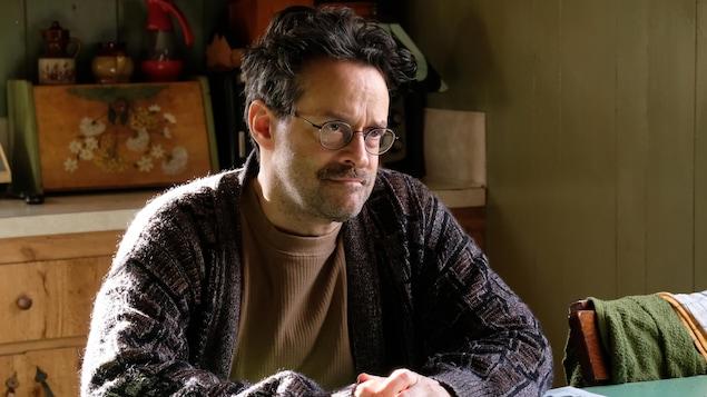 Le comédien Alexis Martin, qui interprète le personnage d'Yvon Dubé dans la série <i>Demain des hommes</i>, lit le journal avec un café.