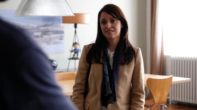 La comédienne, vêtue d'un manteau beige et d'un foulard, se tient debout dans une salle à manger.