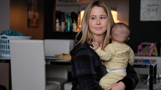 La comédienne tient un bébé dans ses bras.