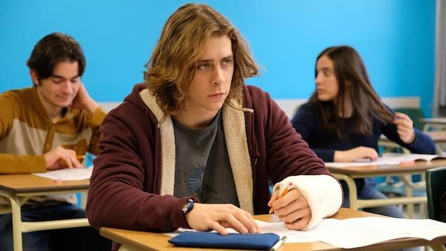 Le comédien, qui a le bras gauche dans le plâtre, prend des notes dans une classe.