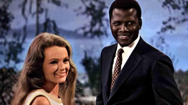Une jeune femme blanche et un jeune homme noir souriants.