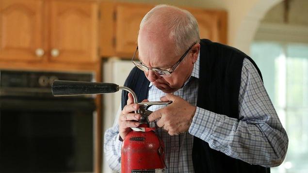 Jean-Pierre Morency qui tente de faire fonctionner l'extincteur de feu.