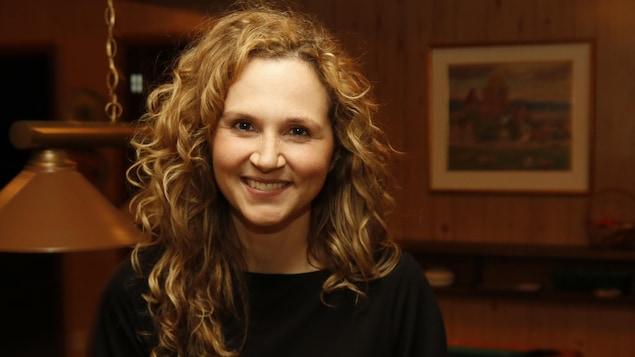 Le personnage de Judith Morency, interprété par Caroline Bouchard, sourit à la caméra tout en étant assise sur une table de billard.