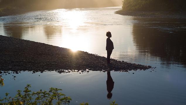 Sur le bord d'une rivière, une femme regarde au loin.