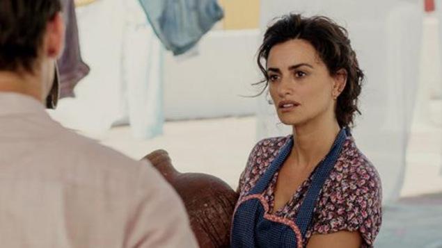 Une femme en tablier, regarde un homme en face d'elle.
