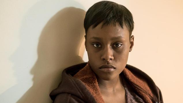 C'est une jeune femme noire. Se cheveux sont courts. Elle porte une veste et un chandail bruns.