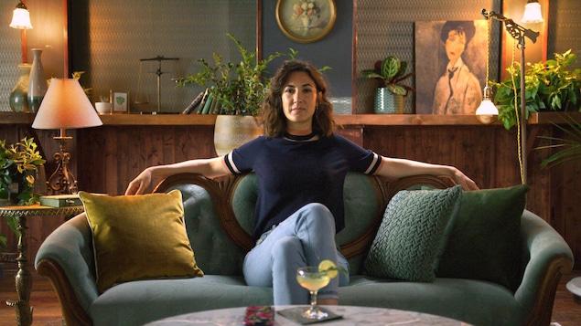 La comédienne est assise dans un canapé, les bras sur le dossier et les jambes croisées.