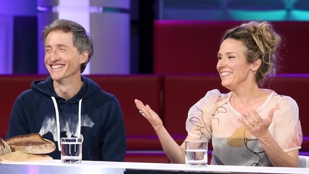 Un homme et une femme qui rient. Quelques pains sont posés sur la table devant l'homme.