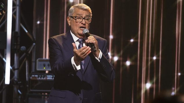 Michel Louvain chante au micro sur la plateau d'En direct de l'univers.