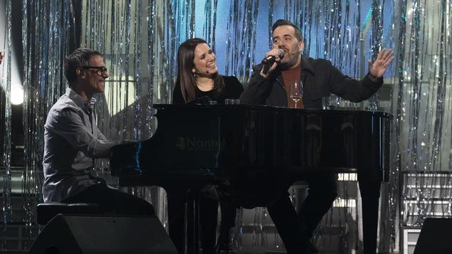 Jean-Sébastien Girard chante au micro assis à côté du piano.