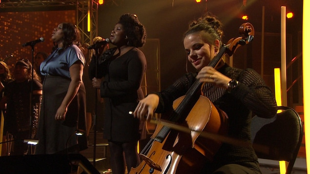 Mélissa Bédard et Yama chantent au micro et Mirianne Brûlé joue du violoncelle.