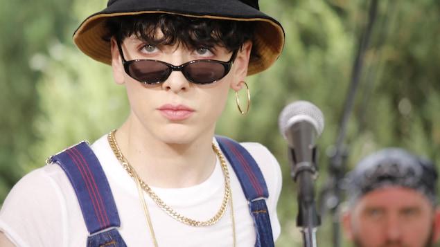 Le chanteur porte un chapeau et des lunettes.