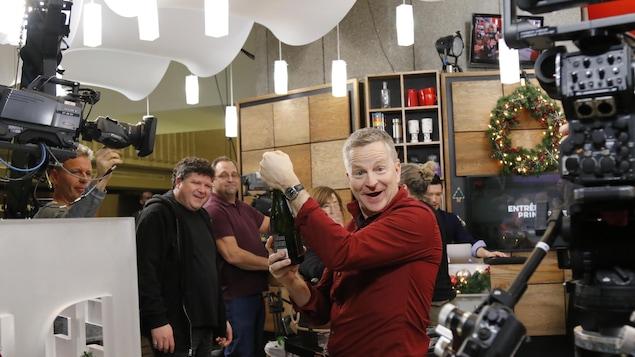 André Robitaille ouvre une bouteille de vin mousseux