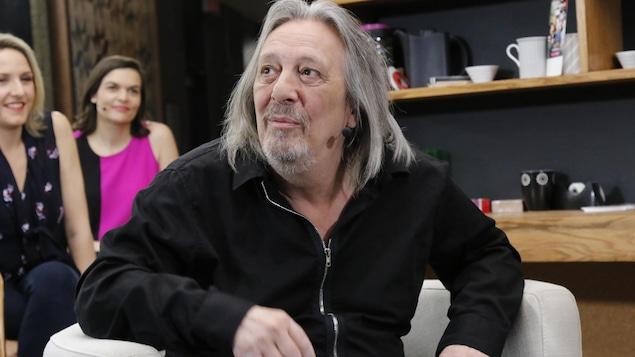 En entrevue, le chanteur regarde un moniteur en studio.