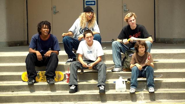 Cinq jeunes skateurs assis sur des marches en pierre.