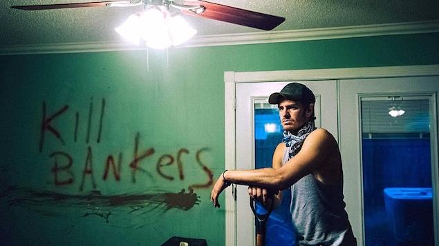 Un homme en débardeur et casquette, la main sur une pelle, dans une maison.