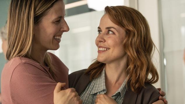 Une jeune femme souriante (Mélanie Charbonneau) prend dans ses bras une autre jeune femme souriante (Noémie O'Farrell).