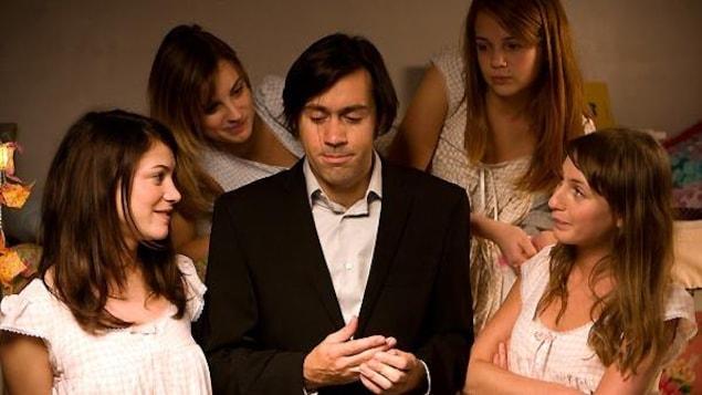 Un homme en costume entouré de quatre jeunes filles en chemises de nuit