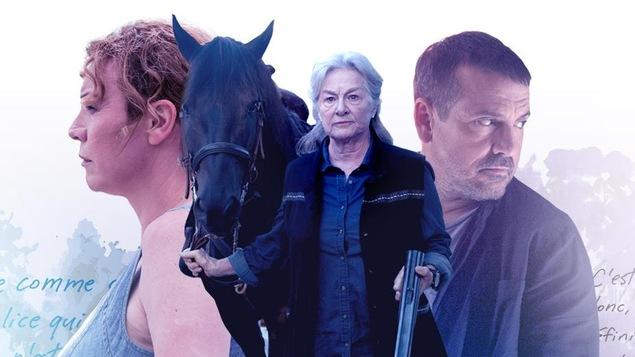 Micheline tient la bride d'un cheval d'une main et un fusil de l'autre