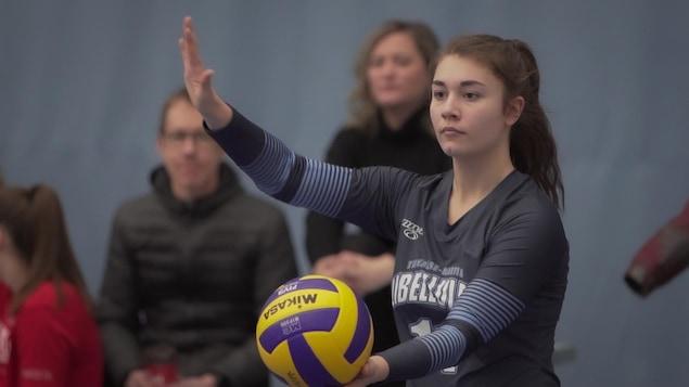 Une jeune femme qui s'apprête à lancer un ballon.