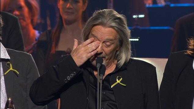 Sur scène, il essuie une larme suite à l'hommage que son groupe a reçu.