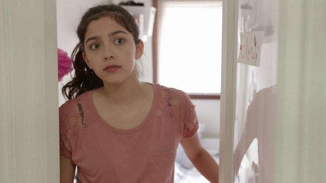 La jeune fille ouvre la porte de sa chambre pour voir ce qui se passe dans le corridor.