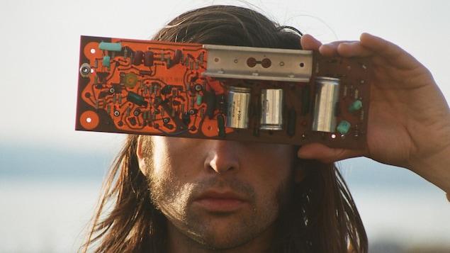 Portrait. Il tient une plaque électronique devant ses yeux.