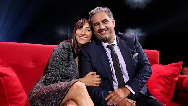 Florence K et Marc Hervieux sur un canapé rouge.