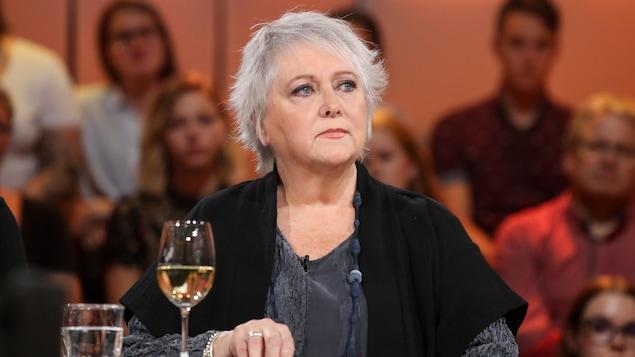 Ses cheveux sont gris et ses yeux bleus. Elle porte une robe grise et une veste noire.