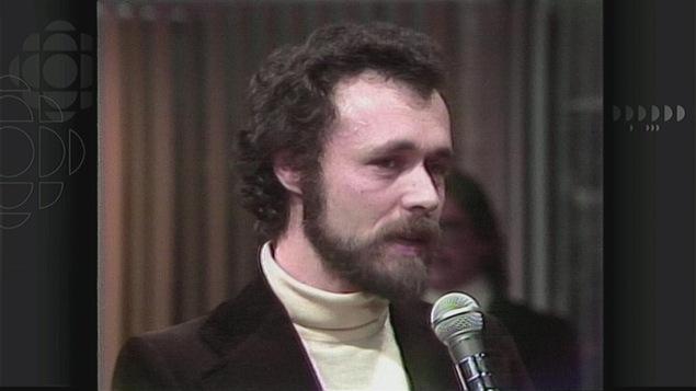 Un homme (Francis Mankiewicz) avec une barbe et un col roulé blanc devant un micro.