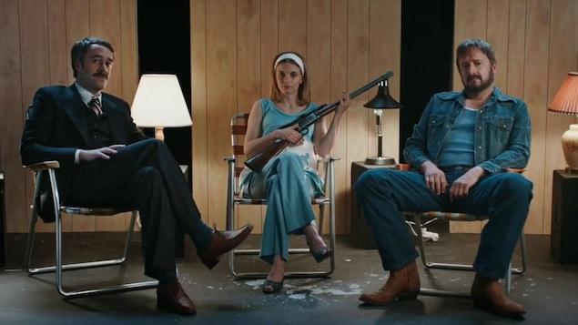 Les trois comédiens dans leurs personnages qui sont assis sur des chaises pliantes.