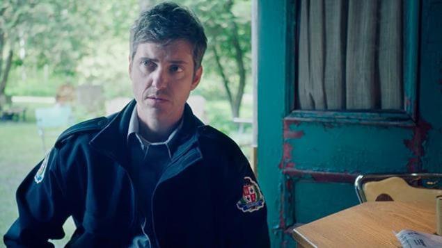 Il porte sa veste de policier.