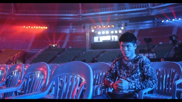 Un homme assit sur une chaise en plastique dans un grand stade.